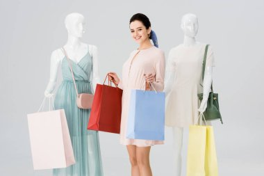 beautiful smiling girl with shopping bags near mannequins isolated on grey