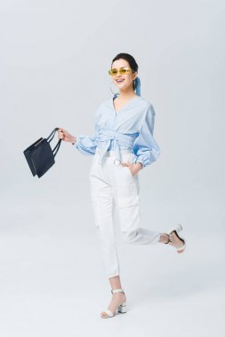 Beautiful stylish young woman in sunglasses holding bag and smiling on grey stock vector