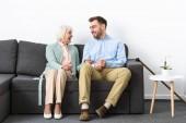 usmívající se starší žena a syn, kteří se dívají na sebe, zatímco sedí na pohovce