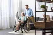 Fotografie lächelnder Mann mit behinderter Seniorin im Rollstuhl