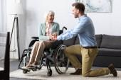 Fotografie Behinderte Seniorin im Rollstuhl und lächelnder Mann, der sich anschaut