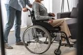 Fotografie beschnittene Ansicht des Mannes, der behinderte Mutter im Rollstuhl trägt