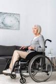 tělesně postiženou starší žena seděla na kolečkovém křesle a dívá se jinam