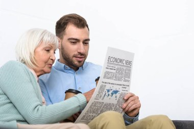 man and senior mother reading newspaper at home