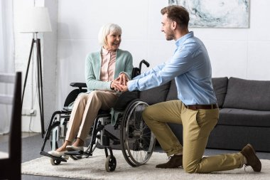 disabled senior woman on wheelchair and smiling man looking at each other