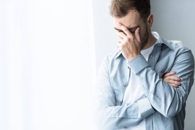 depressed man in blue shirt covering face with hand on at home