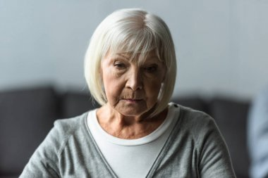 pensive senior woman with grey hair looking down