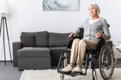 Fotografie disabled senior woman sitting in wheelchair and looking away