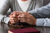 Fotografie partial view of senior woman with rosary holding hands with son