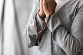 Fotografia partial view of senior woman praying with wooden rosary