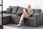 Senior nő a szemüveg ül a kanapén, és olvasás könyv a nappaliban