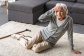 Seniorin mit Migräne auf Teppich sitzend und berührende Stirn mit der Hand