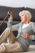 suffering senior woman with heart attack sitting on carpet