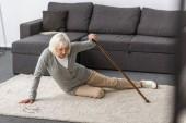 Fotografia sofferenza donna anziana con attacco di cuore sul tappeto