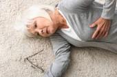 Blick auf kranke Seniorin, die auf Teppich liegt