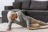 beteg Senior nő nád feküdt a szőnyegen