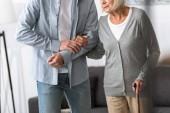 Mann hilft Seniorin zu Hause mit Rohrstock