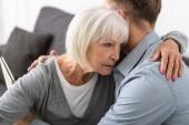 oříznutý pohled muže, který objímá starší matku doma