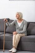 lächelnde Seniorin mit Rohr, die auf dem Sofa sitzt und im Wohnzimmer wegschaut