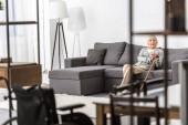 Senior asszony sétapálca ül a kanapén a nappaliban