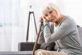 nachdenkliche Seniorin mit Holzrohr sitzen auf Sofa im Wohnzimmer