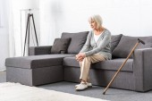 Photo pensive senior woman with wooden cane sitting on sofa in living room