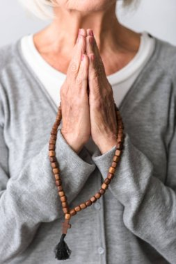partial view of senior woman praying with wooden rosary