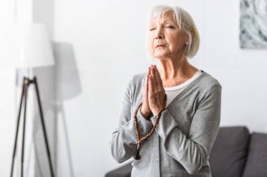 senior woman holding wooden rosary and praying with closed eyes
