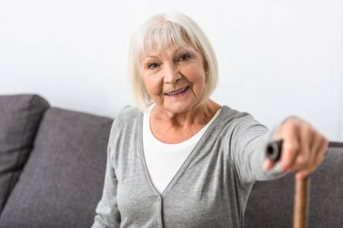 smiling senior woman with wooden cane looking at camera