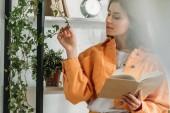 Selektiver Fokus der nachdenklichen jungen Frau mit Buch und anrührender Pflanze im Stehen