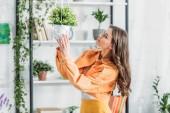 bella giovane donna toccando vaso di fiori mentre in piedi vicino rack in camera spaziosa