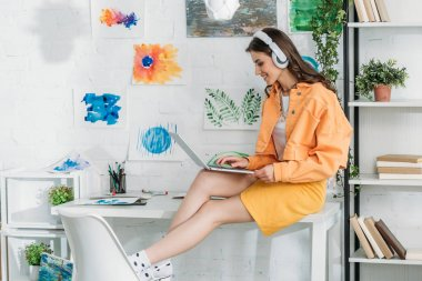 smiling trendy woman in headphones using laptop while sitting on desk