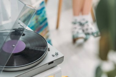 partial view of girl in dotted socks and record player with vinyl disc