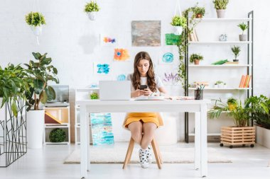 young woman using smartphone while sitting at desk with laptop in spacious room at home