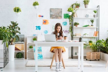 pretty young woman using smartphone while sitting in spacious room with green plants and paintings on wall