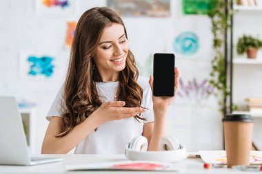 Smiling young woman pointing with hand at smartphone with blank screen.