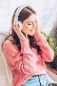 beautiful girl smiling and listening music in headphones with closed eyes