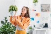 beautiful woman in orange clothing touching hanging flowerpot at home