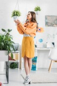 trendy woman in orange clothing touching flowerpot with green plant