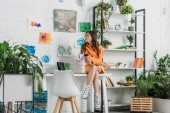 Photo attractive girl sitting on desk and holding paper cup in room decorated with green plants and paintings on wall