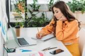 gondolkodó fiatal asszony írás-ban jegyzetfüzet rövid idő ülő-on iskolapad tart laptop és smartphone