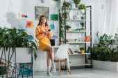 Photo stylish grl using smartphone in spacious room decorated with green plants and colorful paintings on wall