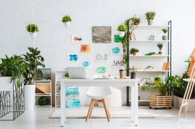 Spacious room with desk, chair, rack, green potted plants and painting on white wall stock vector
