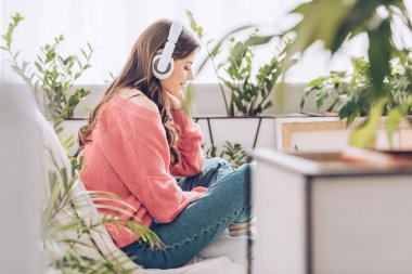 Pensive young woman listening music in headphones while sitting surrounded by green plants at home stock vector