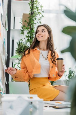 Selective focus of happy young woman holding coffee cup and looking at paintings on wall stock vector