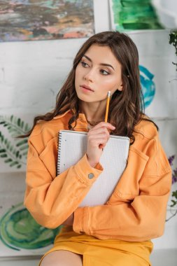 beautiful pensive girl looking away while holding pencil and notebook