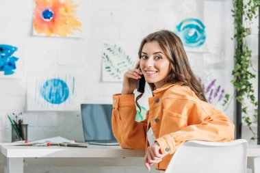 Cheerful girl smiling at camera while sitting at desk by wall with colorful paintings stock vector
