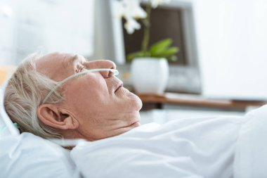 side view of senior man in coma on bed in hospital
