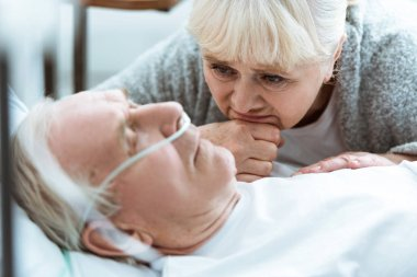 sad senior woman with husband in coma in clinic