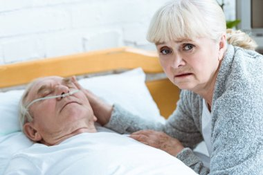 upset senior woman and man in coma in clinic